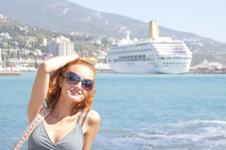 Beautiful smiling woman and cruise ship on background photo