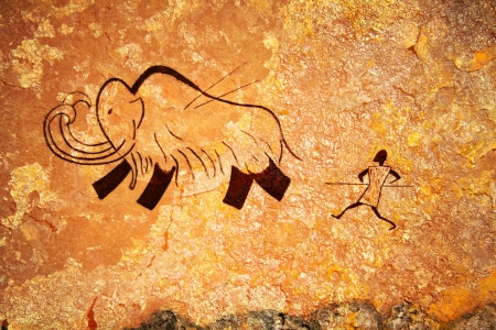Cave painting of primitive man hunting for mammoth photo