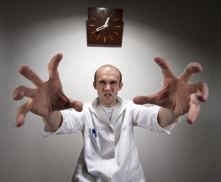 spasms: Ominous angry doctor reaching his long hands Stock Photo