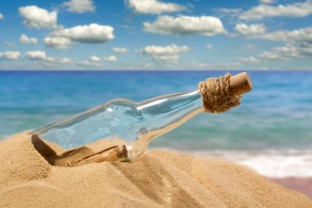 Boodschap in een fles op het strand Stockfoto