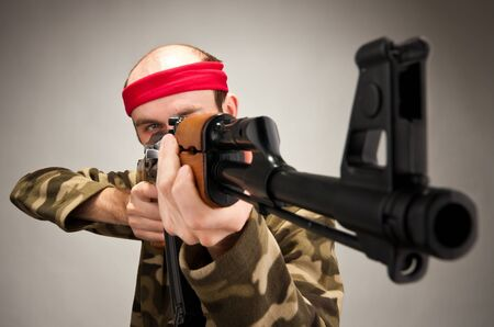 machine man: Portrait of funny soldier aiming with machine gun Stock Photo
