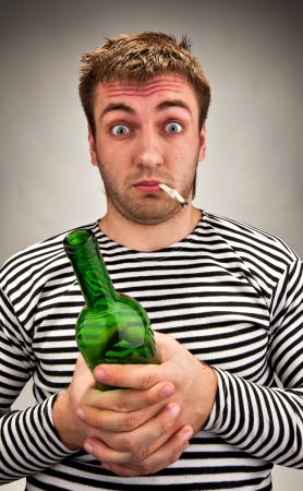 upset man: Drunk bizarre sailor with bottle and cigarette