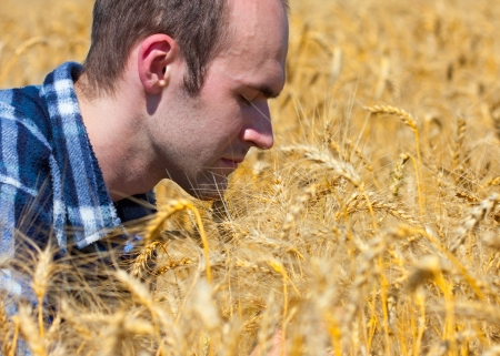 Grateful farmer in wheat field praying for harvest photo