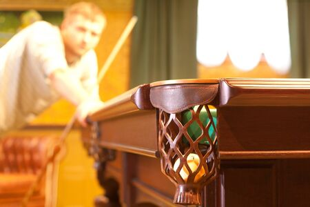 billiards hall: Billiard pocket with ball and player on background Stock Photo