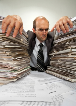 Portrait of serious businessman with big piles of paperwork photo