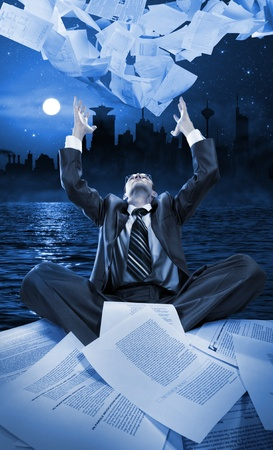 Businessman throwing away papers at night against downtown photo