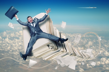 Scared businessman on huge stack of paperwork photo