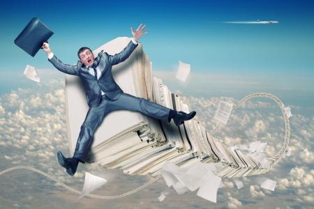 Scared businessman on huge stack of paperwork