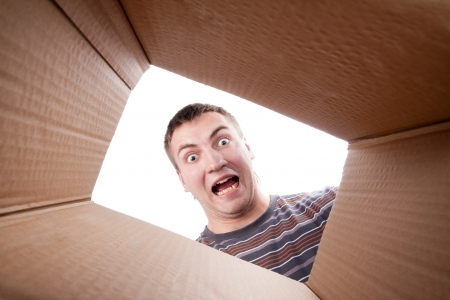 packing supplies: Surprised young man looking into cardboard box