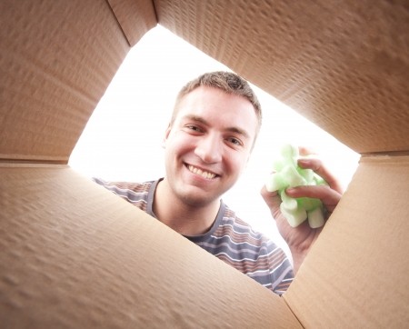 packing supplies: Young man throwing packing polyfoam into cardboard box