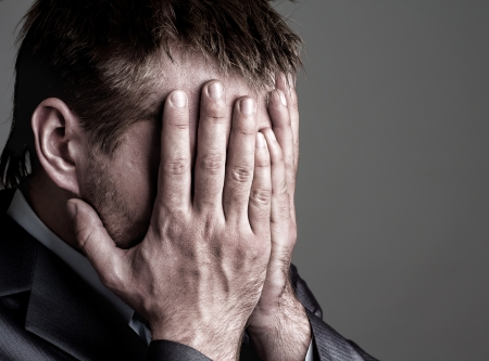 problems solutions: Exhausted sad businessman covering his face by hands Stock Photo