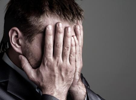 caras de emociones: Exhausto triste hombre de negocios que cubre su rostro con las manos Foto de archivo