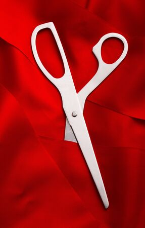 Top view of scissors cutting a red ribbon photo