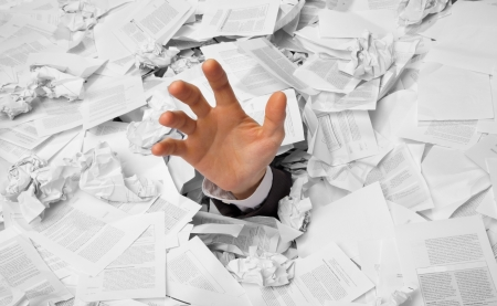 Hand reaches out from big heap of crumpled papers Stock Photo