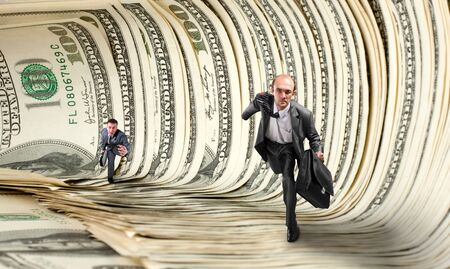 Two serious businessmen running in dollar tunnel photo