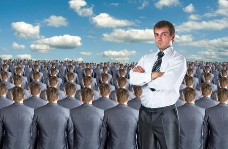 clones: Confident businessman against crowd of business people
