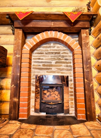 Interior of wooden chalet with small fireplace photo