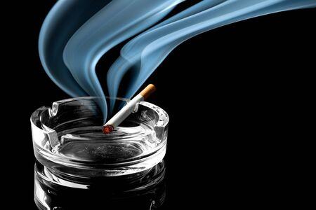 wisp: Close-up van sigaret op asbak met een mooie sliert van rook Stockfoto