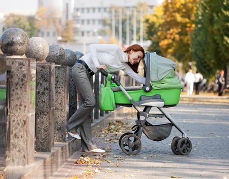 Happy young mother carrying baby in autumn park Stock Photo