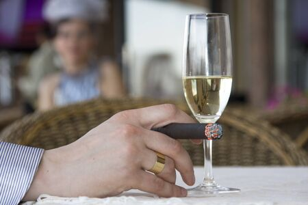 Man in cafe drinking wine and smoking cigar photo