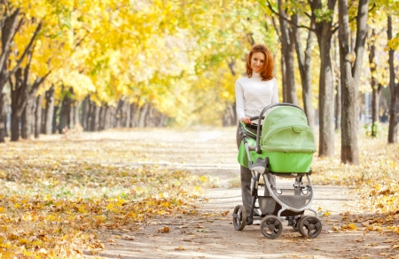 baby stroller: Happy young mother with baby in buggy walking in autumn park