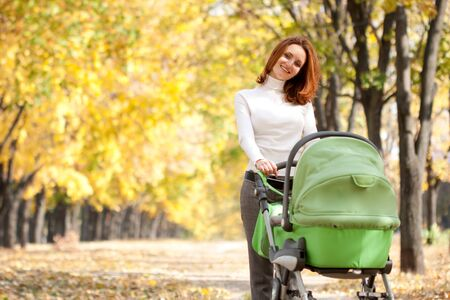 Happy young mother with baby in buggy walking in autumn park photo