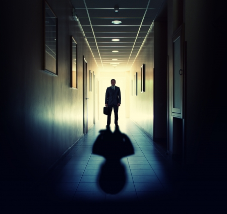 Silhouette of businessman standing in office building corridor against light photo
