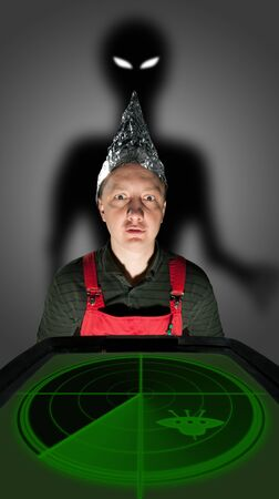 Bizarre man wearing a foil hat and watching old radar monitor with alien shadow behind Stock Photo - 18103469