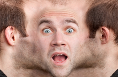 schizophrenia: A panoramic face of very frightened man Stock Photo