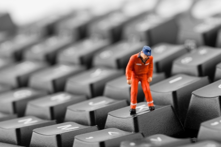 Figurine of worker looking into pit in computer keyboard photo
