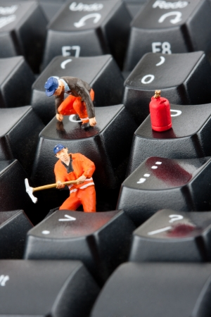 Small figurines of workers repairing computer keyboard photo