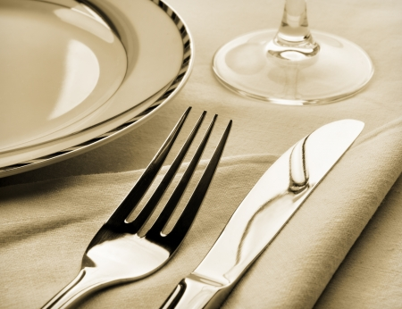 place setting: Dinner set. Fork and knife on napkin. Sepia toned