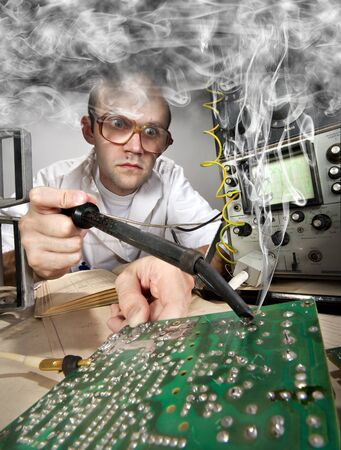 soldering: Funny nerd scientist soldering at vintage technological laboratory Stock Photo