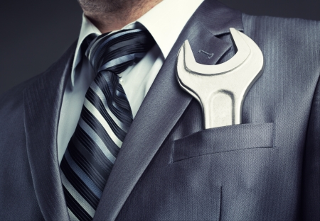 wrench: Businessman with spanner in suit pocket Stock Photo