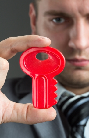 Solution concept - Businessman holding red toy key Stock Photo - 18194958
