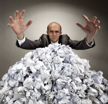 finance a helping hand confusion: Serious businessman with raised hands reaches out from big heap of crumpled papers