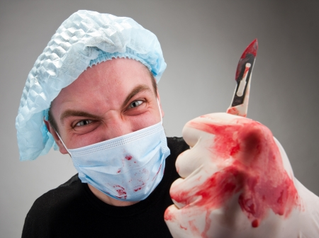 Mad mental sick blood soiled surgeon with knife photo