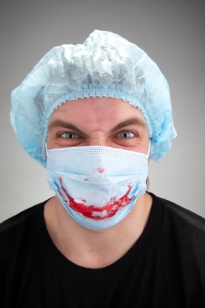 Mad mental sick surgeon with blood smile on mask photo