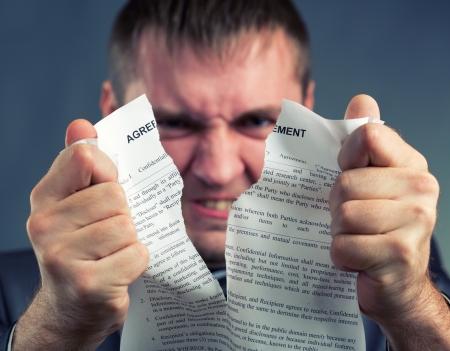 contrato de trabajo: Hombre de negocios enojado acuerdo desgarro en pedazos Foto de archivo