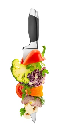 Vegetables on kitchen knife isolated on white photo