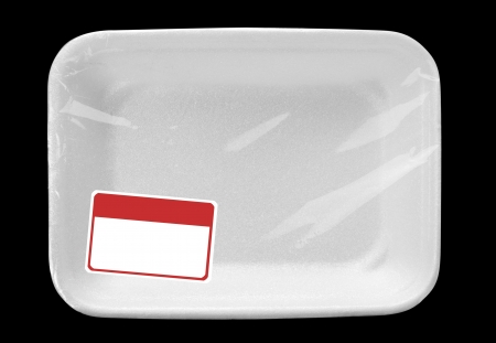 Empty wrapped white food tray with blank label. Isolated on black photo