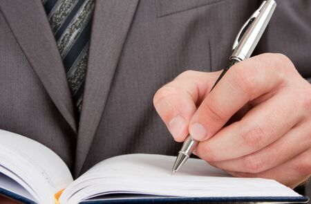Close-up of businessman writing in business diary Stock Photo - 18192297