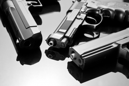 Three handguns. Beretta 92, Desert Eagle and M23 Double Eagle Stock Photo - 18190814