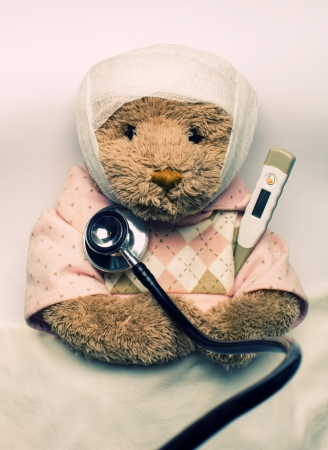 Medical examination of ill teddy bear in bed photo