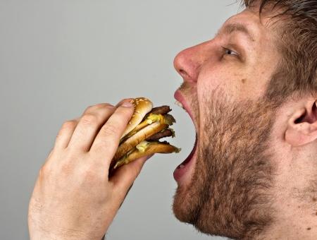 Gros plan d'un homme barbu mangeant hamburger juteux Banque d'images