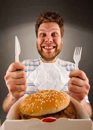 or hungry: Portrait of happy man with knife and fork ready to eat burger