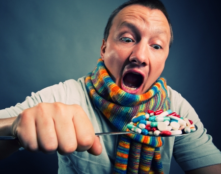 Man eating pills and medicines with big spoon Stock Photo - 18195019