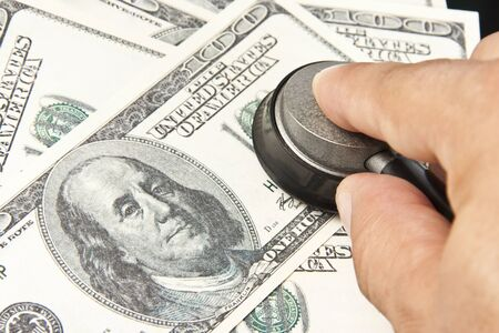 Examination of the US dollars. Businessman with stethoscope Stock Photo - 18194191
