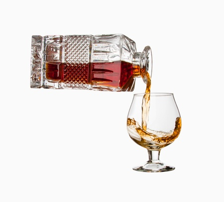 intoxicate: Pouring cognac from bottle into a glass. Isolated Stock Photo