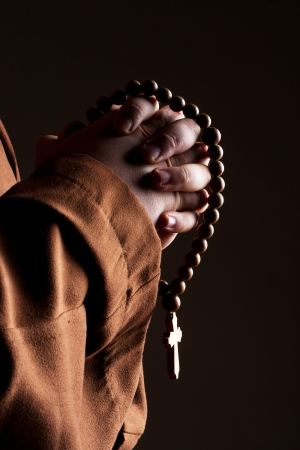 theology: Monk in robe with two hands clasped in prayer Stock Photo